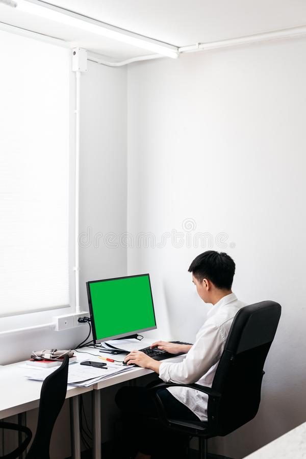 Tillbaka av den b?rande vita skjortan f?r man och att sitta p? svart kontorsstol och att arbeta med hans persondator med gr?n sk? royaltyfria foton