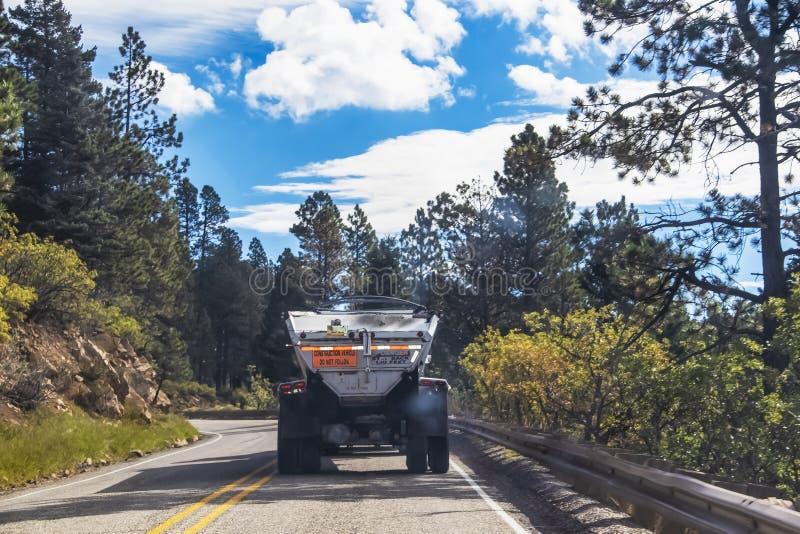 Tillbaka av dumper som sänder ut rök bak och damm överst som kör på den curvy bergvägen - selektiv fokus arkivfoto