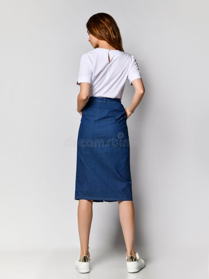 Tillbaka av en ung brunettflicka med l?ngt h?r i en vit blus och en bl? kjol P? en ljus bakgrund arkivbilder