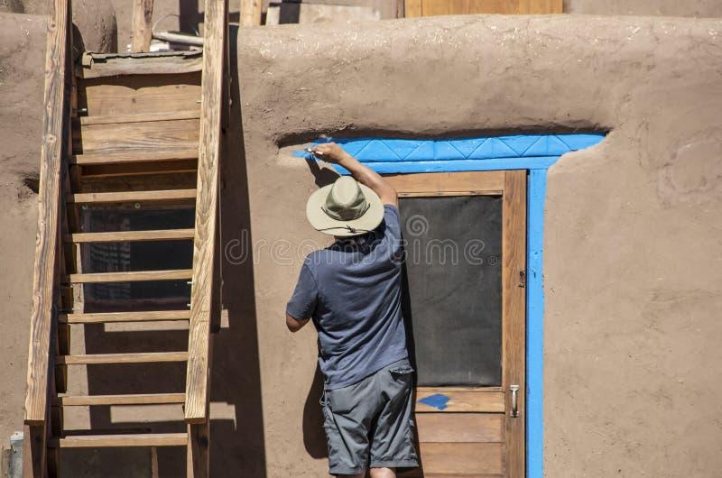 Tillbaka av indianmannen i kortslutningar och denskjorta och solhatten som målar ljus blått-turkos runt om dörren av en gyttjaAdo royaltyfria foton