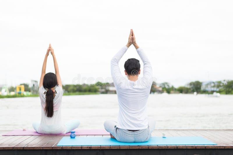 Tillbaka av mannen och den övande yoga och meditationen för kvinna på mattt nära lagun fotografering för bildbyråer