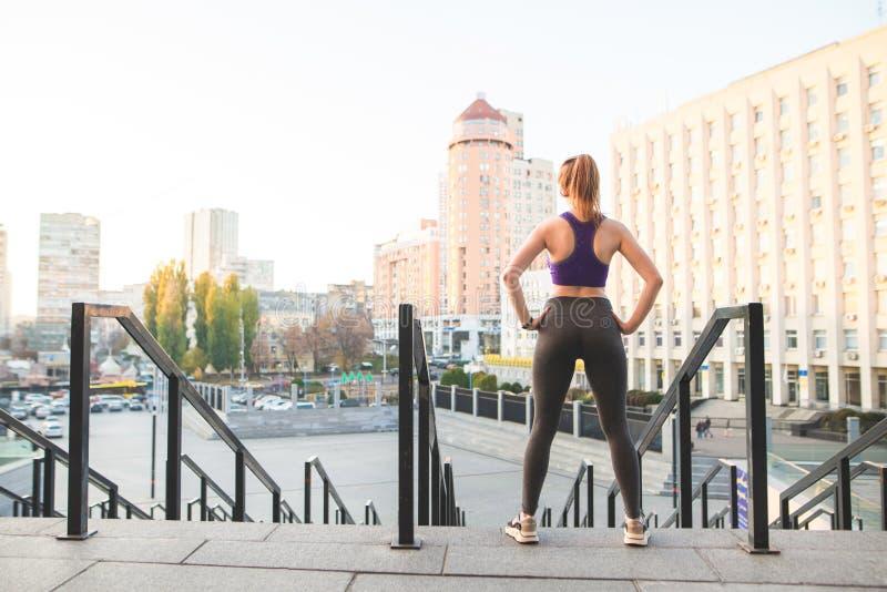 Tillbaka av sportar står rymmer en flicka i överkant och damasker mot bakgrunden av staden och händer på bältet royaltyfri foto