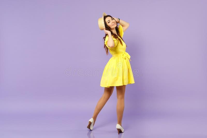Tillbaka bakre sikt av den nätta unga kvinnan i den gula klänningen som sätter händer på sommarhatten som ser tillbaka isolerad p royaltyfri foto