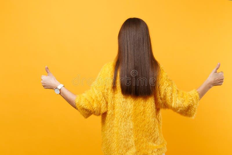 Tillbaka bakre sikt av den unga kvinnan för brunett i fördelande händer för pälströja som visar tummar som isoleras upp på ljus g arkivbild