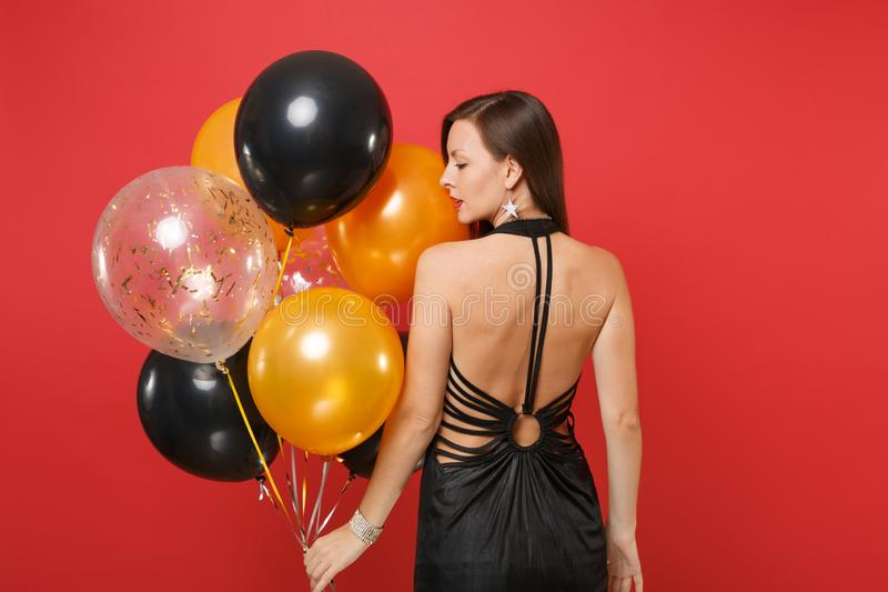 Tillbaka bakre sikt av unga flickan i liten svart klänning som firar att se rymma åt sidan luftballonger isolerade på rött arkivfoton