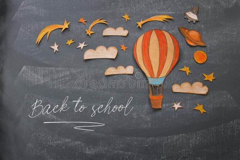 tillbaka begreppsskola till Ballong för varm luft, snitt för utrymmebeståndsdelformer från pappers- och som målar över klassrumsv royaltyfria foton