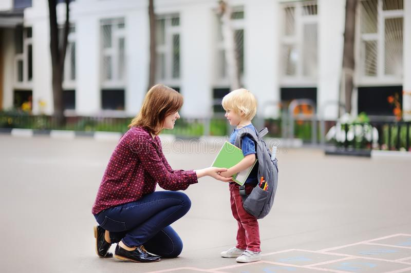 tillbaka begreppsskola till Liten elev med hans unga moder Första dag av grundskola för barn mellan 5 och 11 år royaltyfri bild