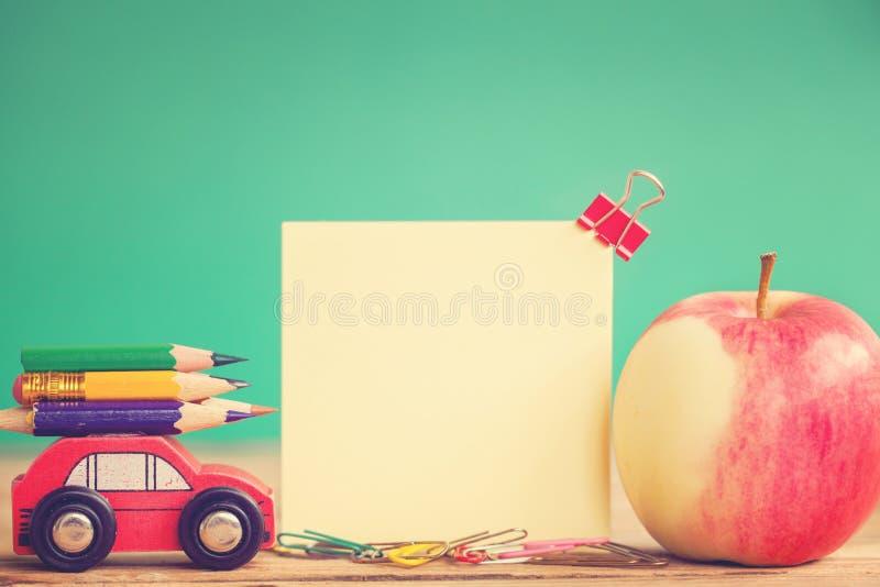tillbaka begreppsskola till Miniatyrrött bära för bil färgrika blyertspennor och rött äpple på trätabellen tona bild royaltyfria bilder