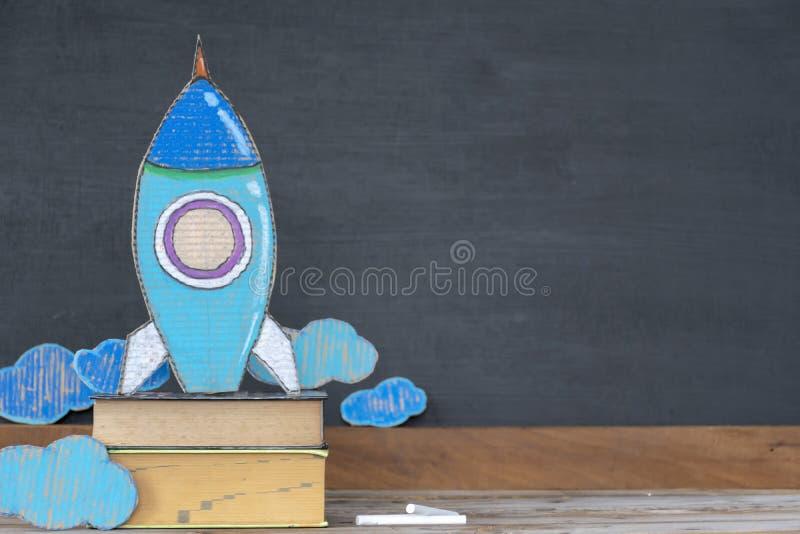 tillbaka begreppsskola till Pappers- raket lokaliseras på böcker royaltyfri fotografi