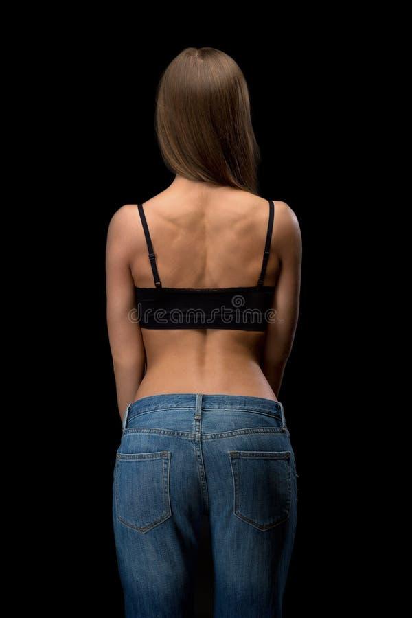 tillbaka blå flickajeans arkivfoto