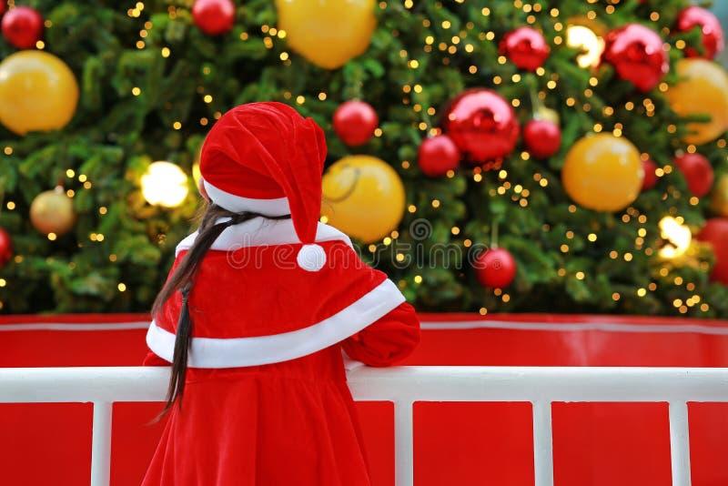 Tillbaka flicka för litet barn för sikt i jultomtendräkten som ser julgranen Begrepp för julvinterferie royaltyfri bild