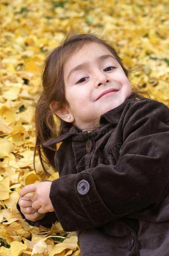tillbaka flicka som little lägger leaves över yellow arkivbilder