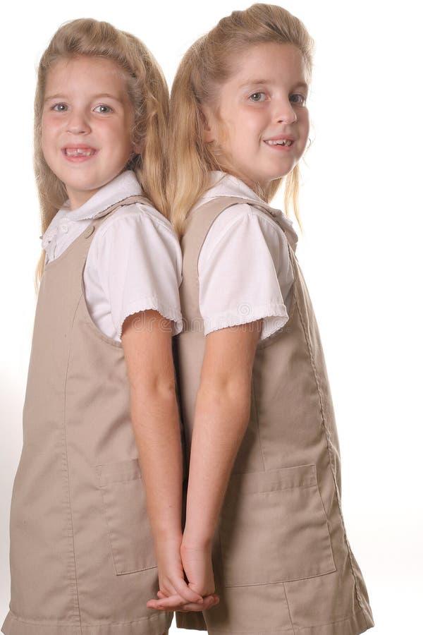 tillbaka flickahänder som rymmer tvilling- vertical för skola royaltyfri bild