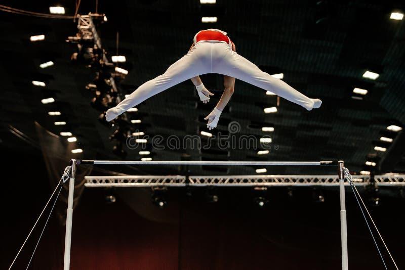 tillbaka gymnastövning på horisontalstänger arkivfoto