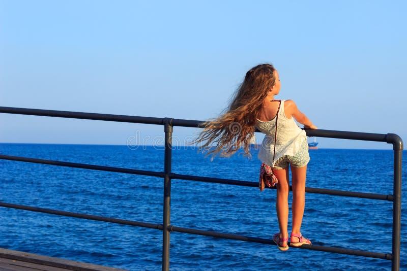 Tillbaka härlig liten tonårig flicka med flödande länge lockigt hår in fotografering för bildbyråer