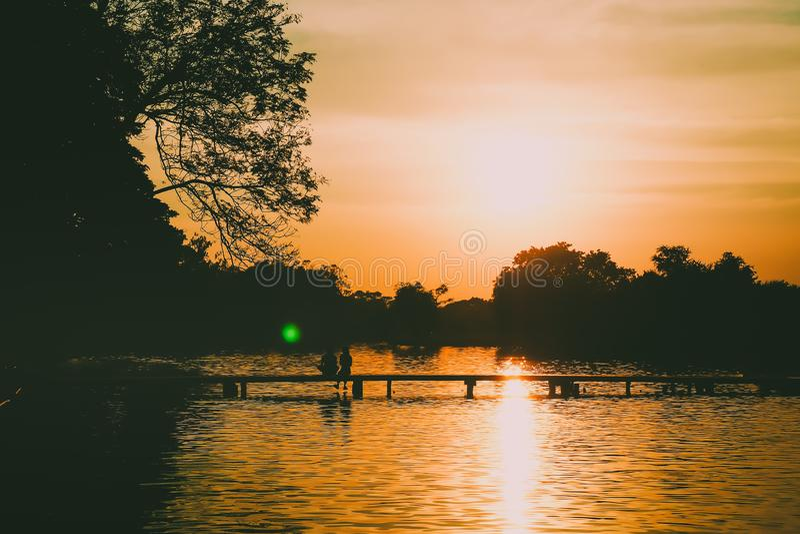 Tillbaka kontur av ett par som sitter på bron som rymmer den härliga skogsjön för händer på solnedgångbakgrund royaltyfria foton