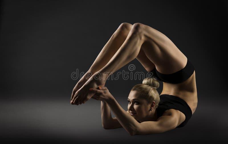 Tillbaka krökning som sträcker ställing, böjande kvinnaakrobatgymnastik fotografering för bildbyråer