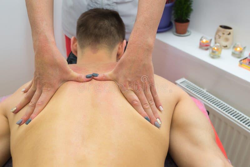 tillbaka massage Massösterapeut som tillbaka masserar region för överkant av en manlig idrottsman nen arkivbilder