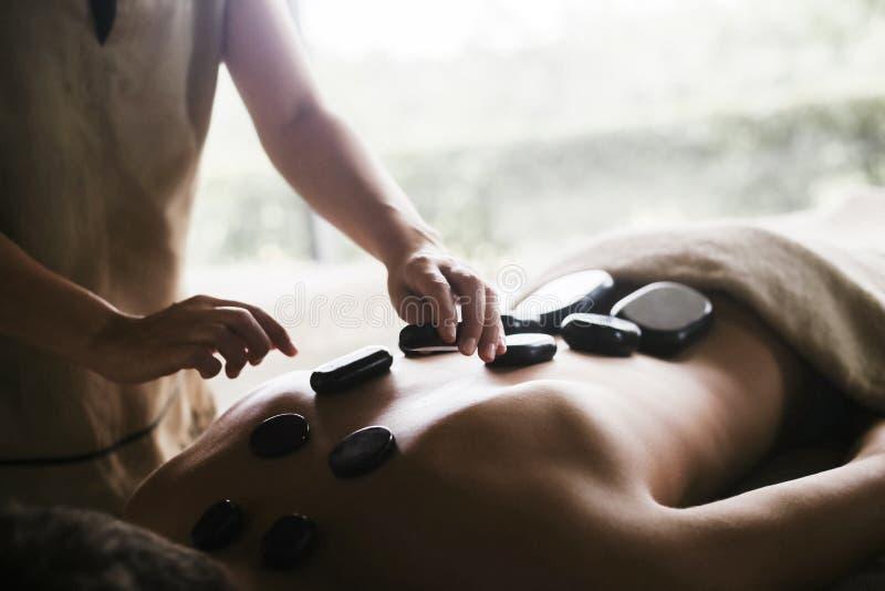 Tillbaka massage med olja och varma stenar royaltyfri fotografi