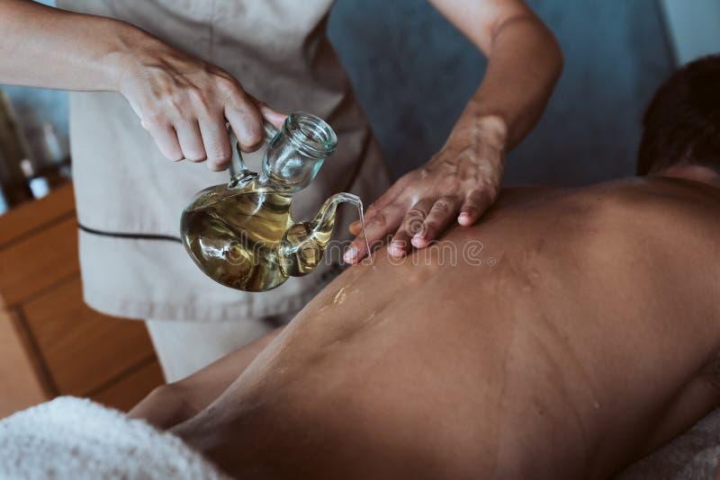 Tillbaka massage med olja och varma stenar royaltyfria bilder