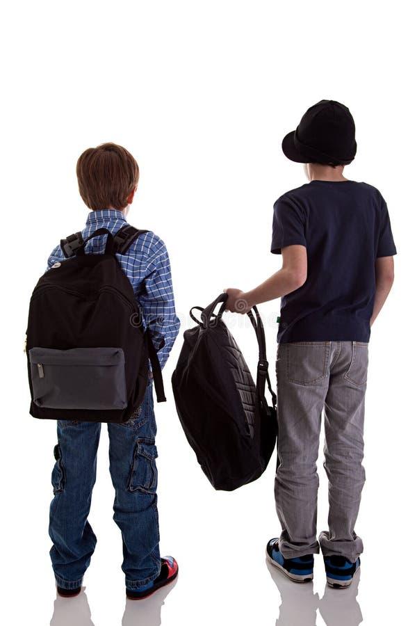 tillbaka ryggsäckholdingschoolboy royaltyfria foton