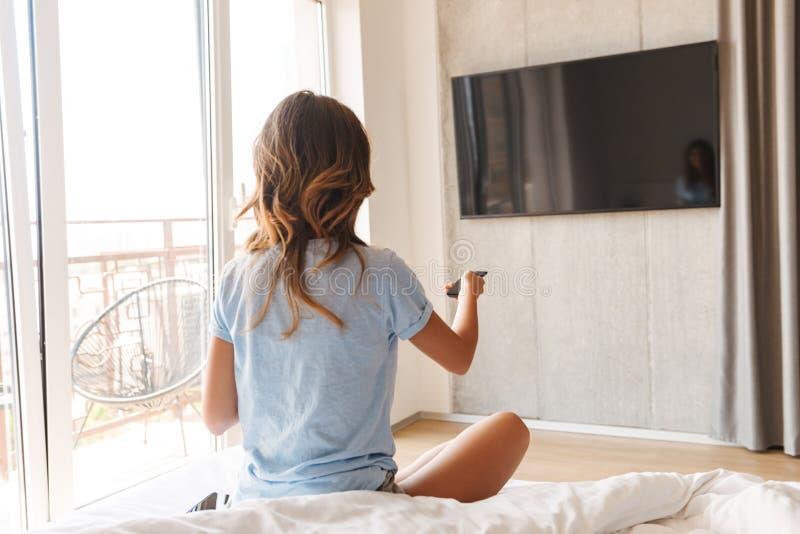 Tillbaka sammanträde för ung kvinna för sikt på säng arkivbilder