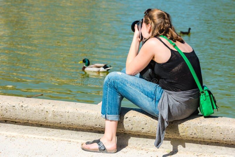 Tillbaka sida av den unga kvinnan som tar ett foto royaltyfria bilder