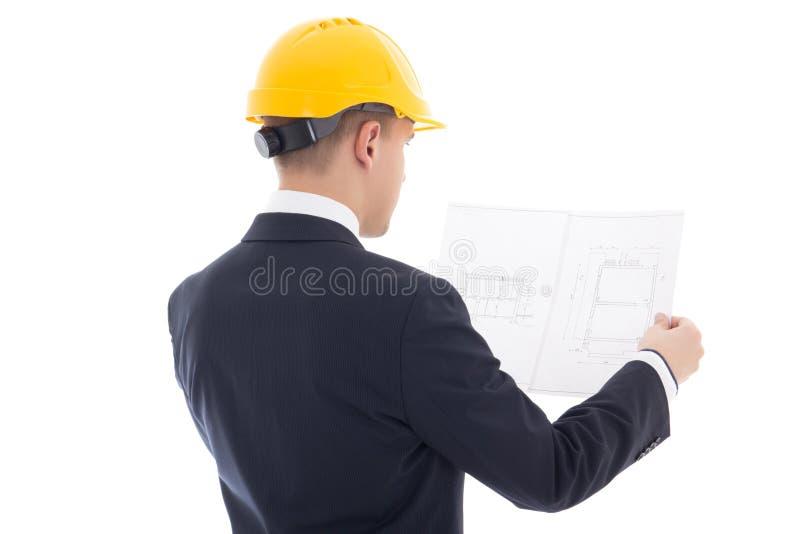 Tillbaka sikt av affärsmannen i gula byggmästares hjälm med bluepr arkivbilder