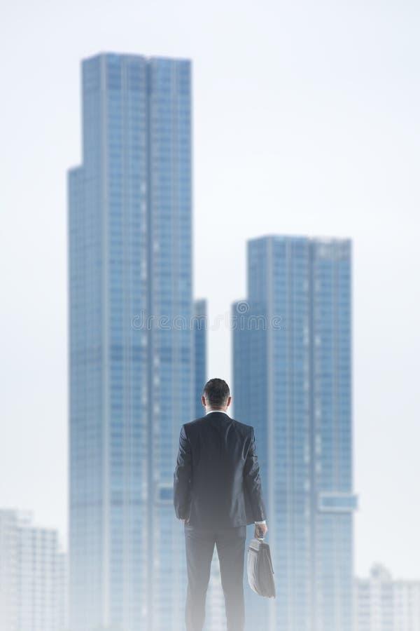 Tillbaka sikt av affärsmannen som ser på skyskrapa arkivbilder