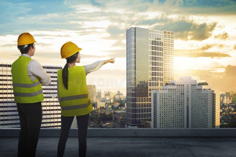 Tillbaka sikt av arkitekt som två ser staden arkivbild