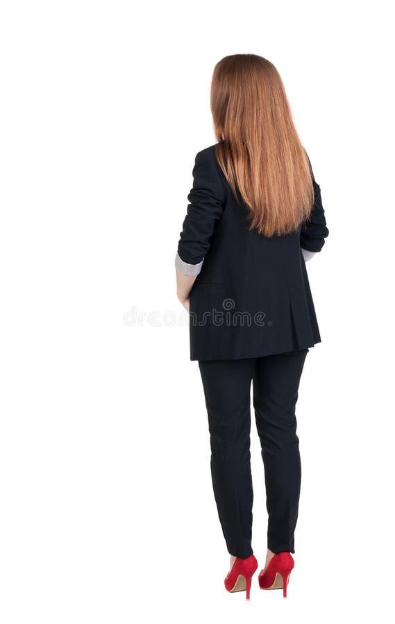 Tillbaka sikt av att beskåda för rödhårig manaffärskvinna arkivfoto