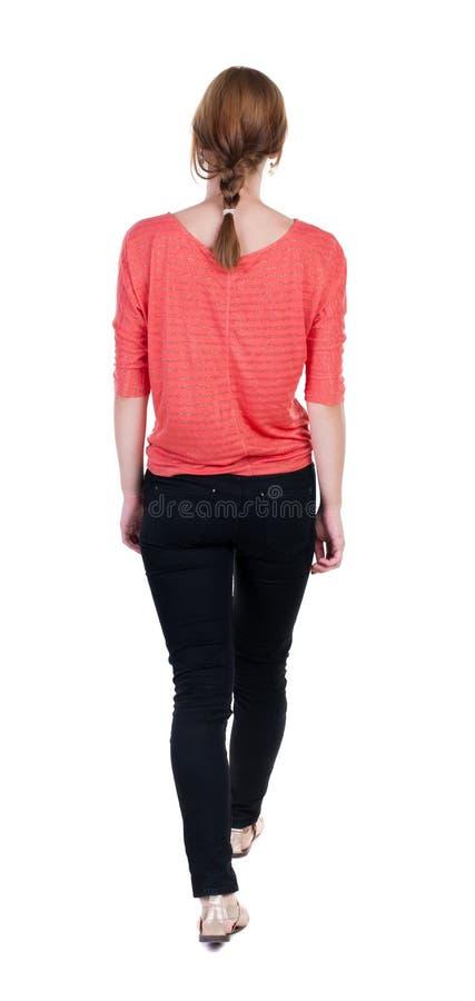 Tillbaka sikt av att gå kvinnan i jeans härlig blond flicka i M royaltyfria foton