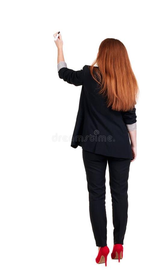 Tillbaka sikt av att skriva den härliga rödhårig manaffärskvinnan arkivbild