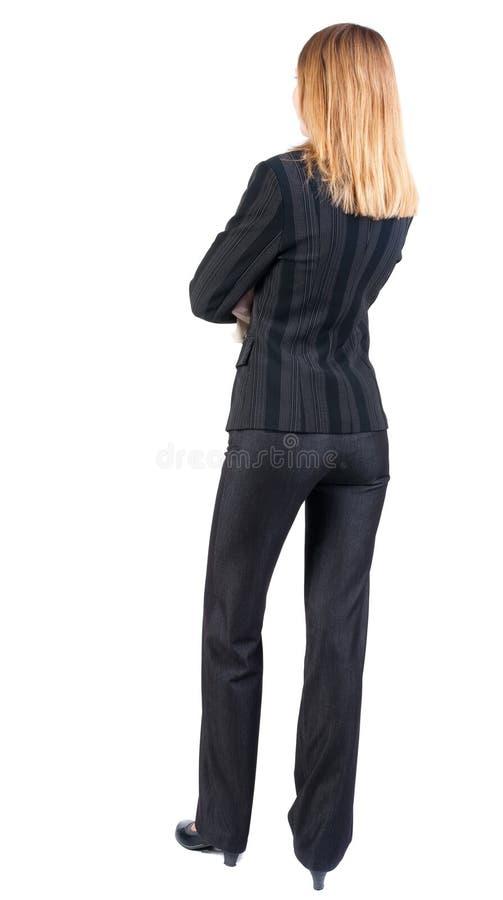 Tillbaka sikt av att stå den härliga blonda affärskvinnan royaltyfri bild