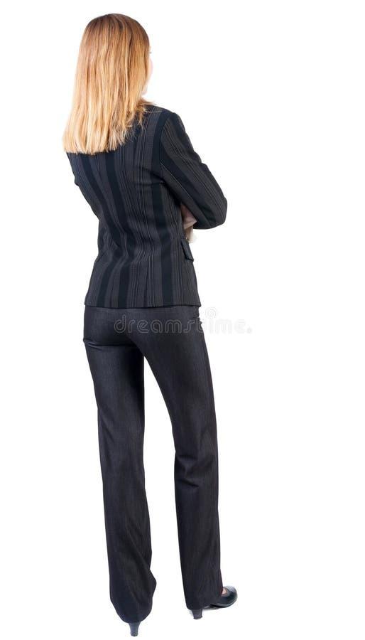 Tillbaka sikt av att stå den härliga blonda affärskvinnan arkivfoto
