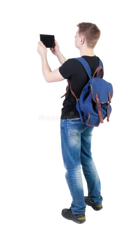 Tillbaka sikt av att stå den unga mannen med minnestavladatoren och backpac royaltyfri bild