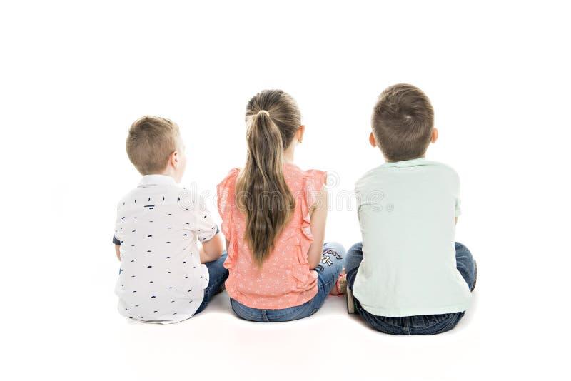 Tillbaka sikt av barngruppen som sitter på golvet som ser väggen arkivfoto