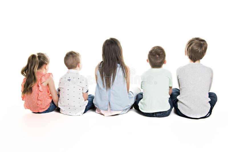 Tillbaka sikt av barngruppen som sitter på golvet som ser väggen arkivbild