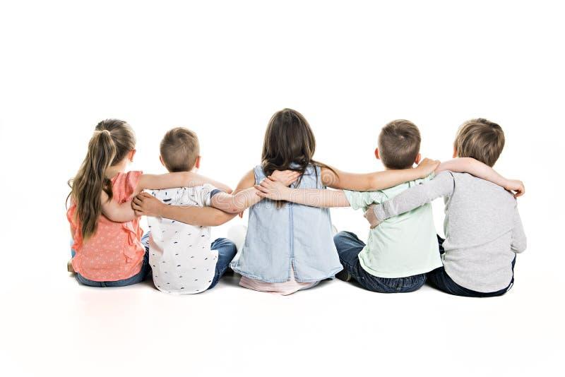 Tillbaka sikt av barngruppen som sitter på golvet som ser väggen fotografering för bildbyråer