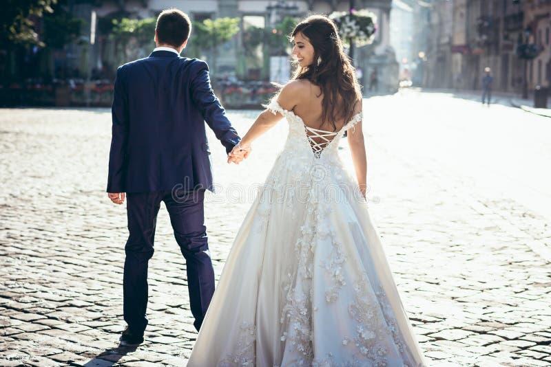 Tillbaka sikt av brudgummen som leder den härliga le brunettbruden i klänningen med det kalt tillbaka längs det soligt royaltyfri fotografi
