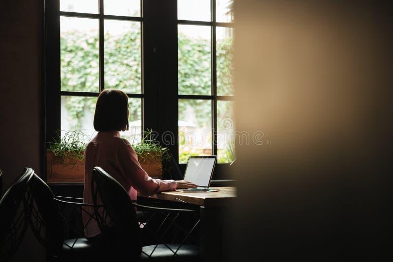 Tillbaka sikt av brunettkvinnasammanträde vid tabellen nära fönster royaltyfri fotografi