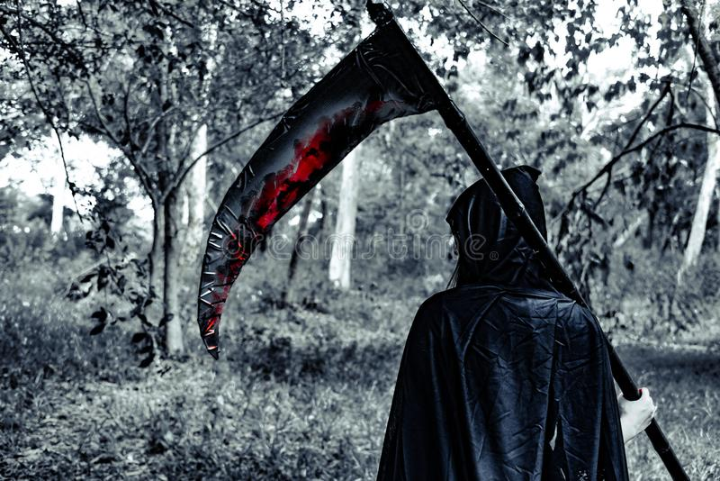 Tillbaka sikt av demonhäxan med skördemaskinen och blod i gåtan fo arkivfoton