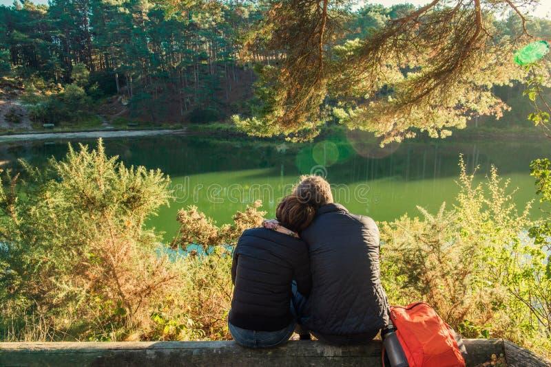 Tillbaka sikt av den älskvärda den parmannen och kvinnan som sitter nära skogsjön som kramar och kopplar av Utomhus- begrepp för  arkivfoto