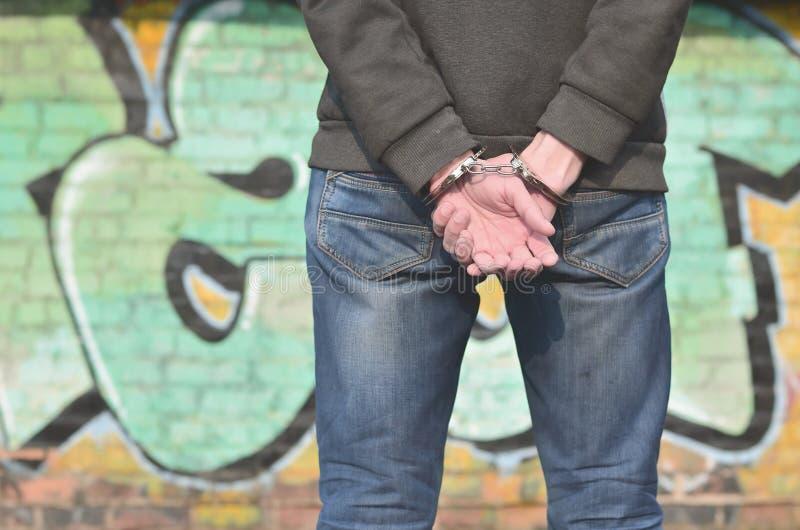 Tillbaka sikt av den arresterade banditen fr?n gettot mot graen arkivbild
