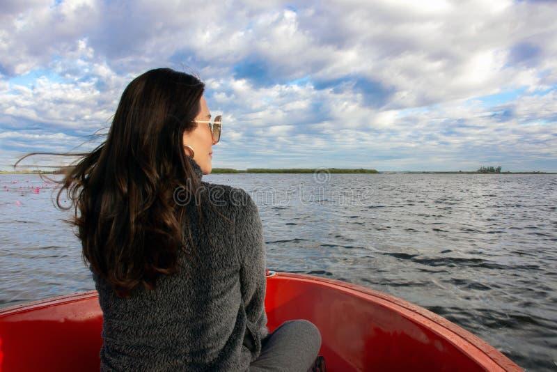 Tillbaka sikt av den asiatiska kvinnan att tycka om på fartyget och att se framåtriktat in i lagun arkivfoto