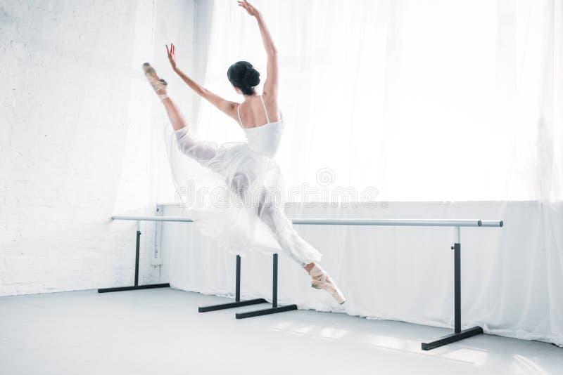 tillbaka sikt av den behagfulla unga ballerina i den vita klänningdansen i balettstudio royaltyfri foto