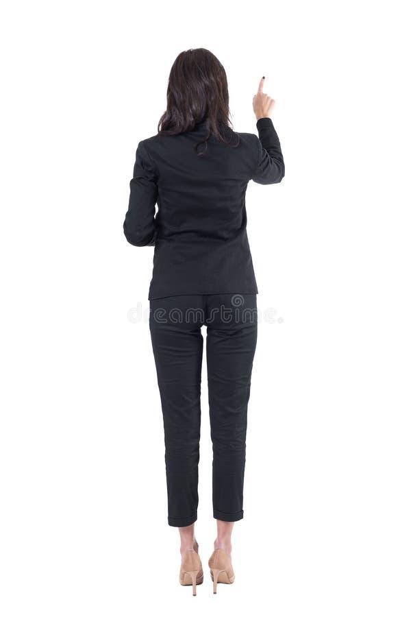 Tillbaka sikt av den eleganta läraren eller affärskvinnan som pekar den skjutande knappen för assistent på pekskärmen royaltyfria bilder