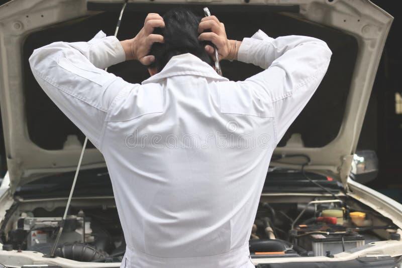 Tillbaka sikt av den frustrerade stressade unga mekanikermannen i den vita likformign som trycker på hans huvud med händer mot bi royaltyfri foto