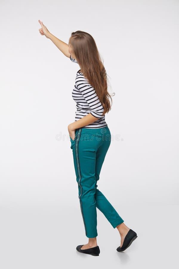 Tillbaka sikt av den fulla längdaffärskvinnan, i att peka på kopieringsspac fotografering för bildbyråer