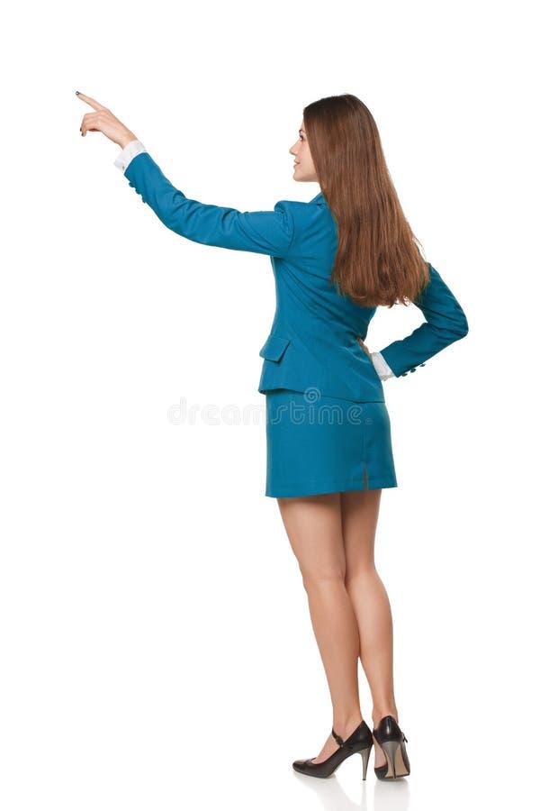 Tillbaka sikt av den fulla längdaffärskvinnan, i att peka på kopieringsutrymme som isoleras på vit arkivfoton
